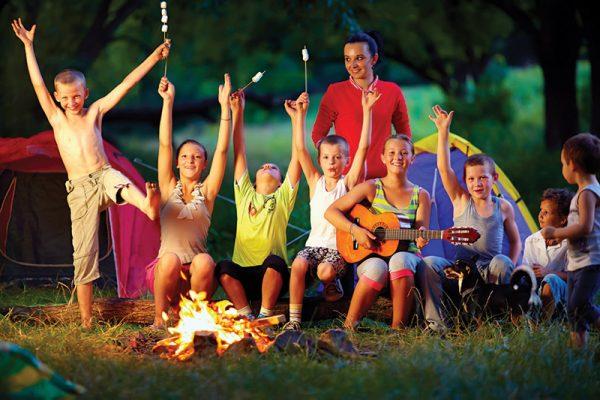 Деца играят край огъня с учител
